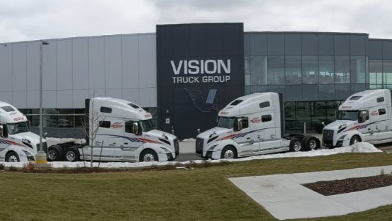 line of white trucks at vision truck group campus570x322