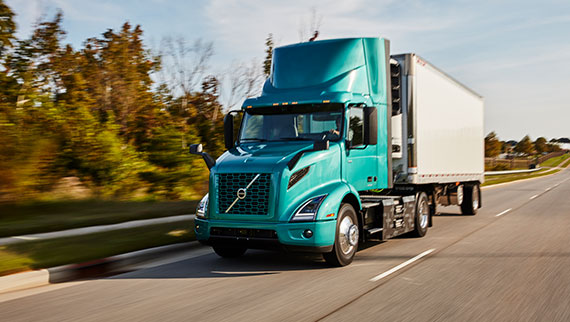 Volvo VNR Electric 4x2 with Reefer Trailer Driver Side View On the Road