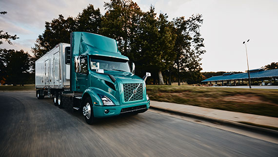 Volvo VNR Electric 6x2 Tractor with Reefer Trailer Passenger Side View on the Road Daytime Shot